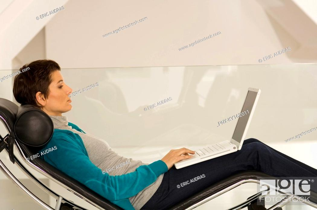 Stock Photo: Businesswoman reclining on a chaise longue and using a laptop.