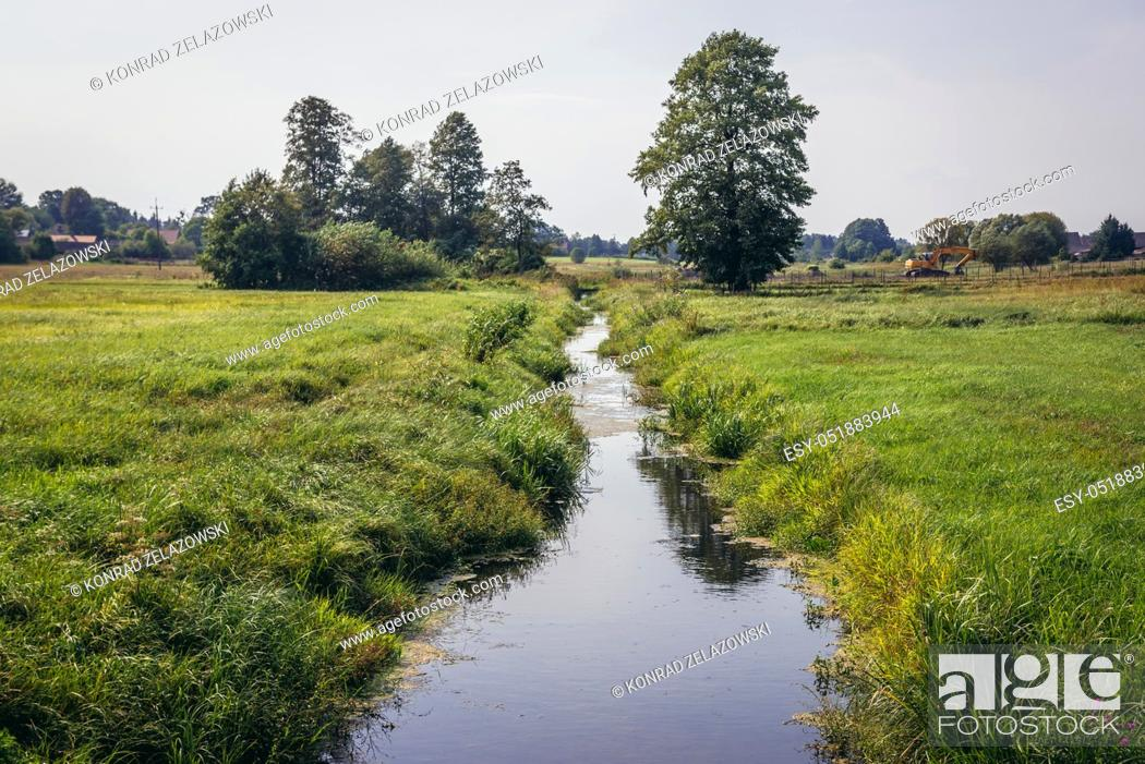Stock Photo: Rudnia river in Soce village on so called The Land of Open Shutters trail, famous for traditional architecture in Podlaskie Voivodeship, Poland.