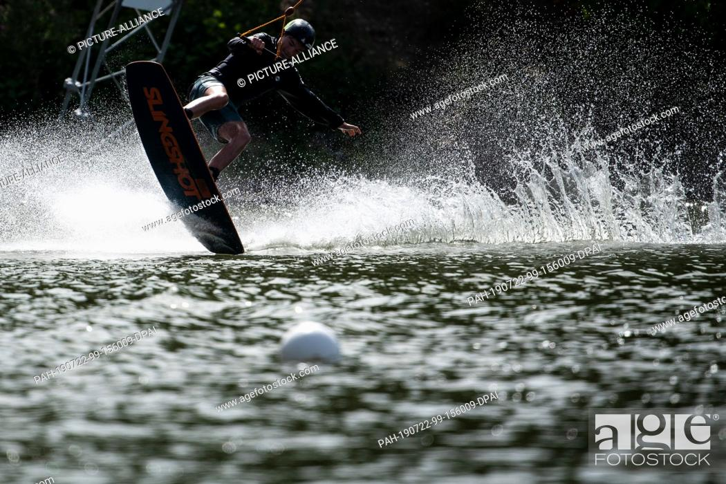 Stock Photo: 22 July 2019, North Rhine-Westphalia, Langenfeld: Water splashes as a wakeboarder on a water ski facility drives through a bend.