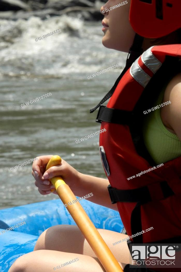Stock Photo: Side profile of a young woman rafting in a river.