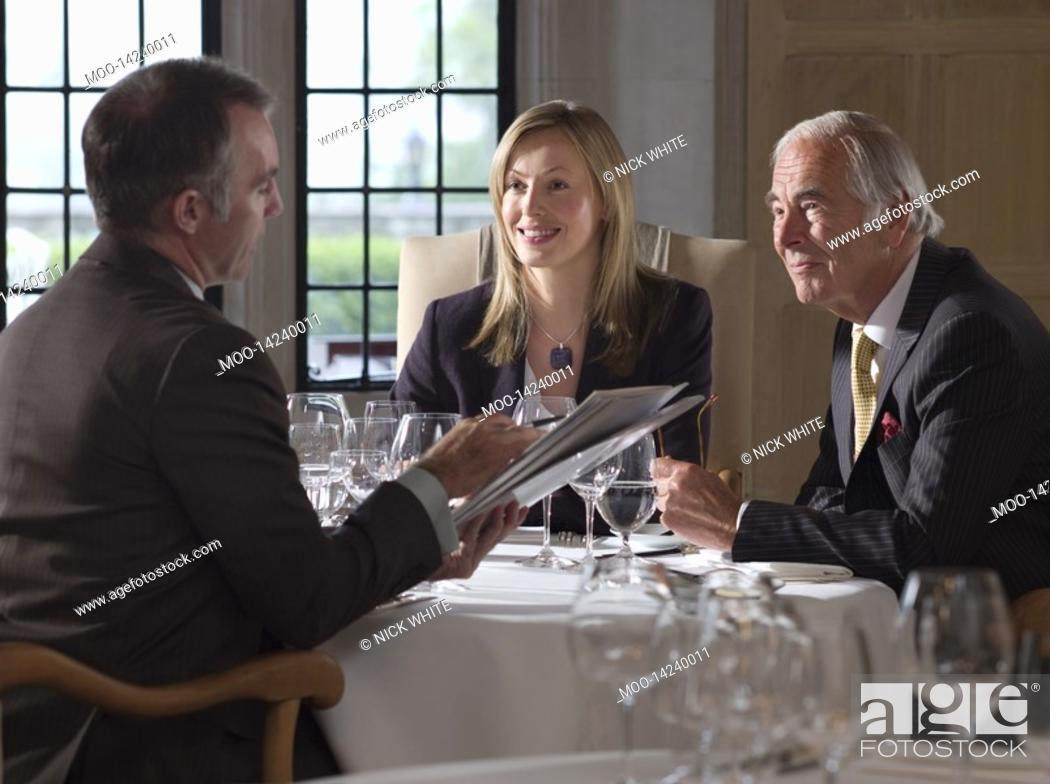 Stock Photo: Three business people sitting at restaurant table one man holding documents.
