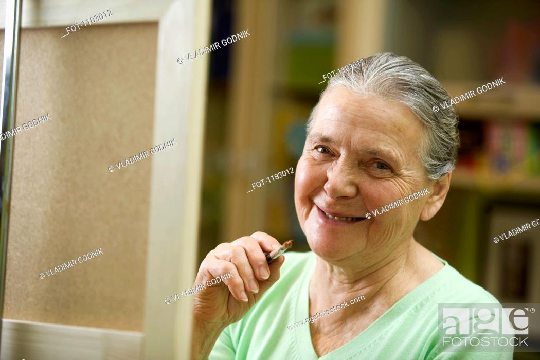 Stock Photo: A cheerful senior woman holding a paintbrush.