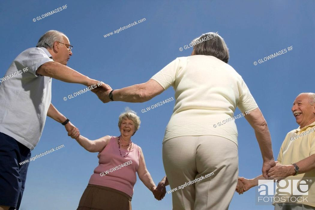 Stock Photo: Low angle view of senior people holding hands of each other.