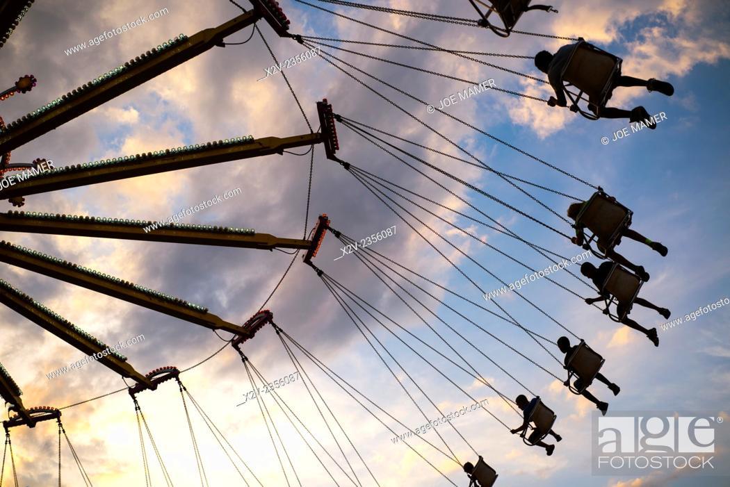 Photo de stock: An amusement ride at a county fair sends riders soaring through the air at sunset.