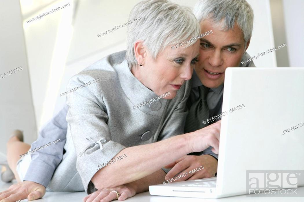 Stock Photo: Mature couple looking at laptop in airport.