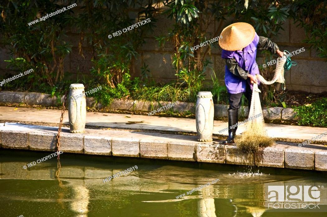 Stock Photo: Fisherman holding a fishing net, Guilin, Guangxi Province, China.