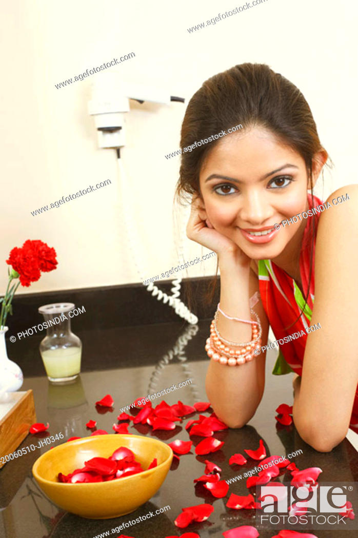 Stock Photo: Portrait of a young woman leaning on the table and smiling.