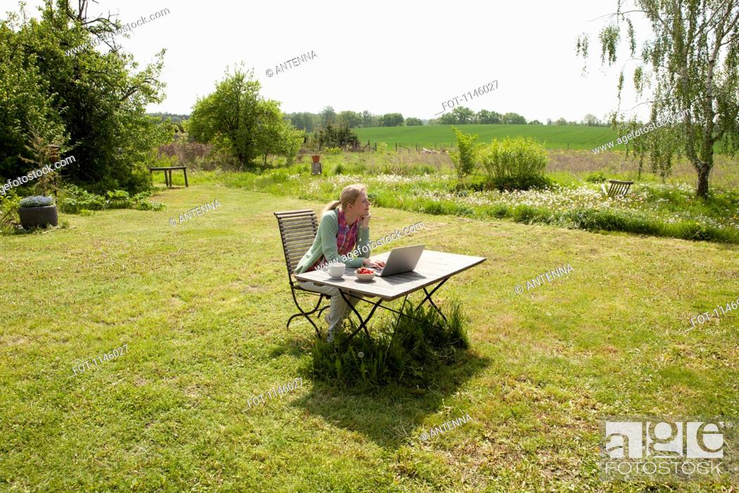 Stock Photo: A woman with a laptop sitting at a table in her back yard, rural setting.