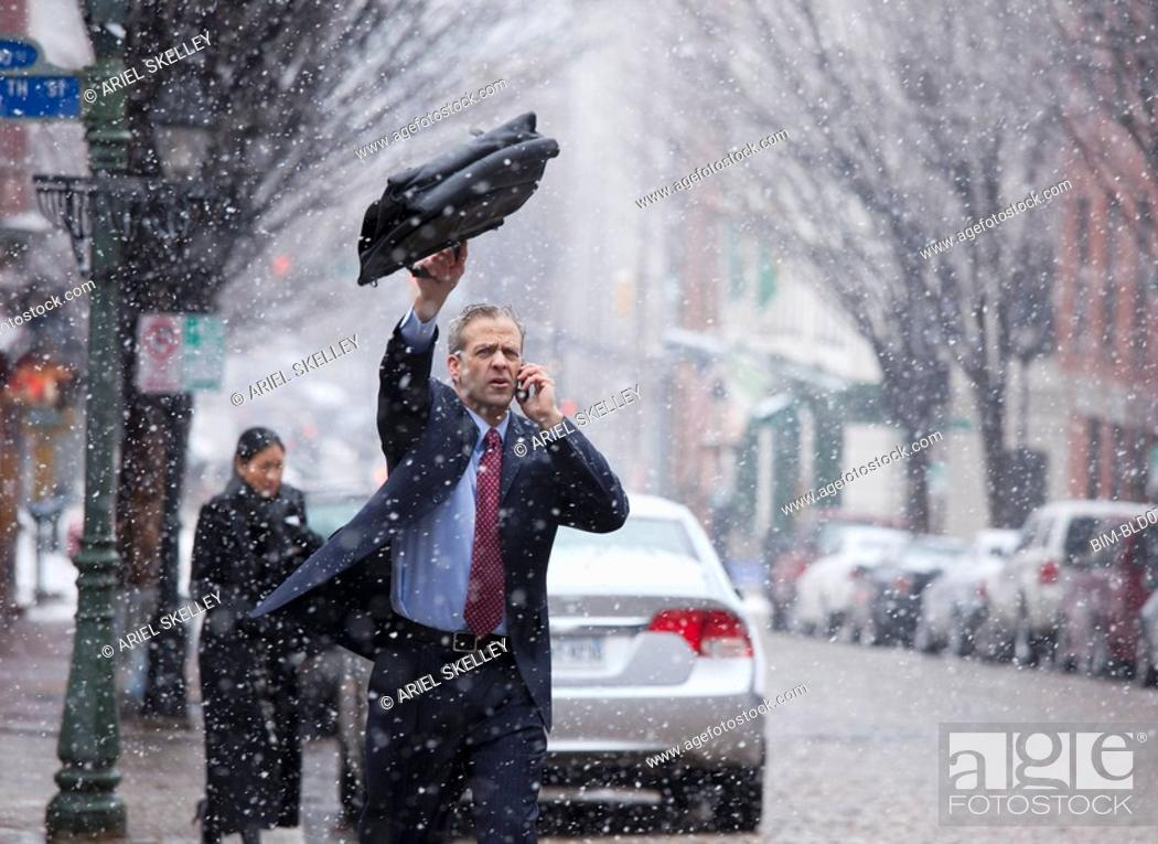 Stock Photo: Caucasian businessman hailing taxi in snow.