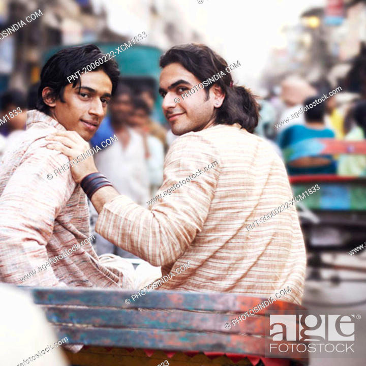 Stock Photo: Rear view of two young men sitting in a rickshaw.
