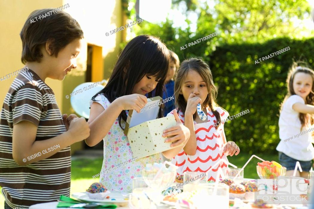 Stock Photo: Girl opening gift at birthday party as friends watch.