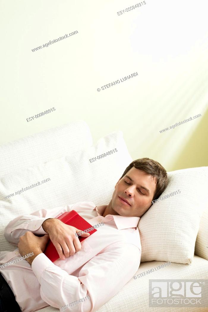 Stock Photo: Tired man asleep on the couch.