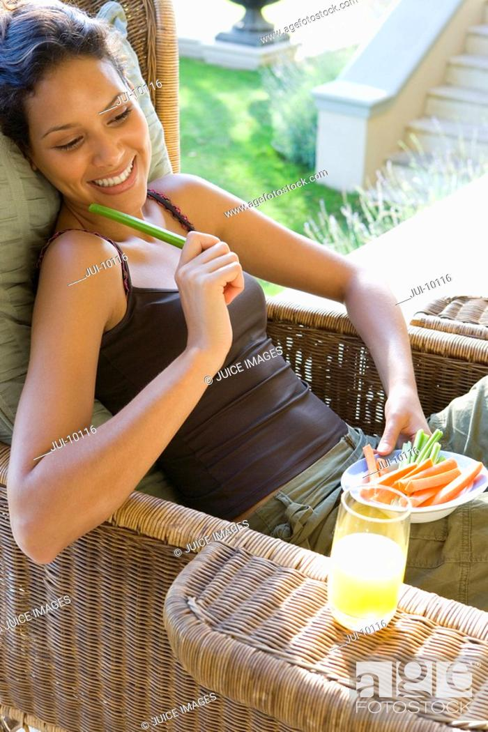 Stock Photo: Young woman with plate of vegetable sticks in armchair outdoors, smiling, elevated view.