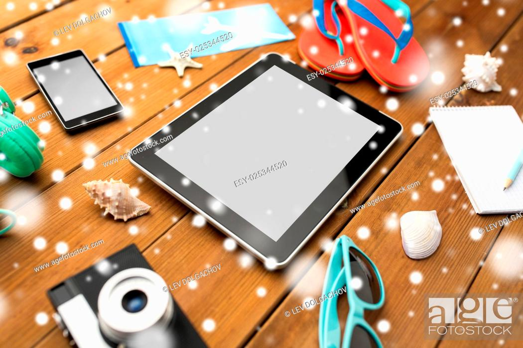 Stock Photo: winter holidays, tourism, technology and objects concept - close up of tablet pc computer and travel stuff over snow.