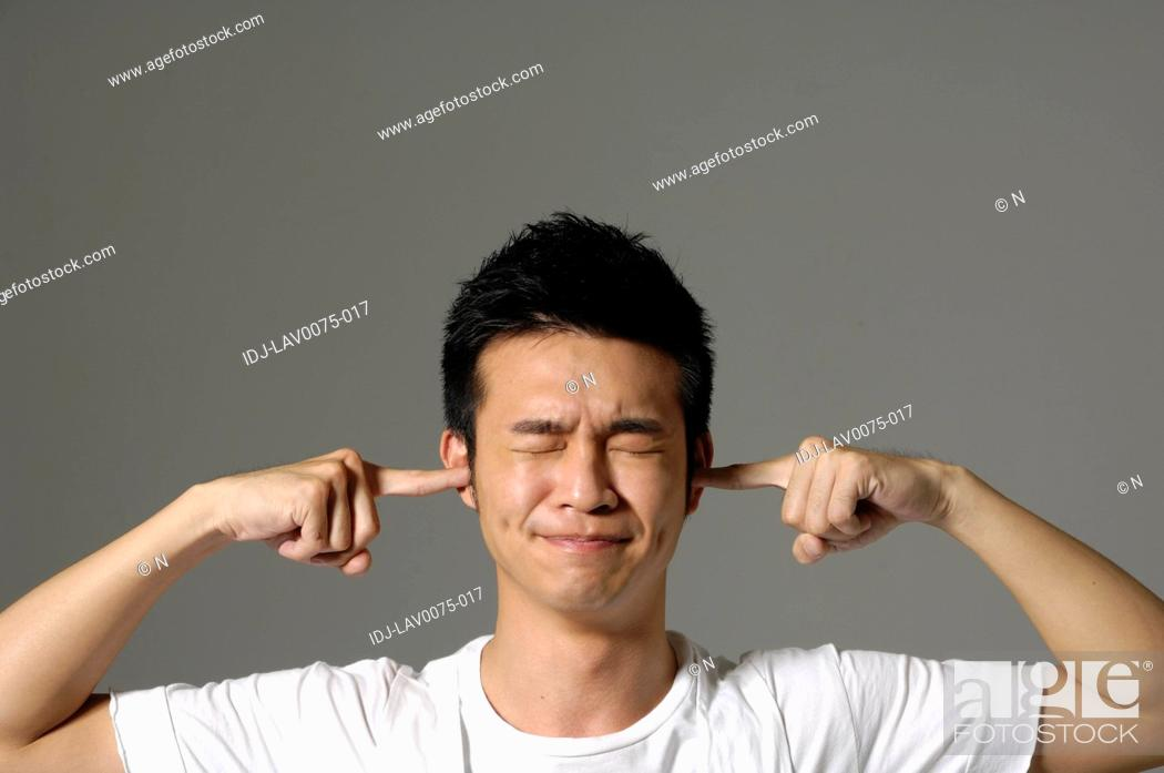 Stock Photo: Male university student with fingers in ears.