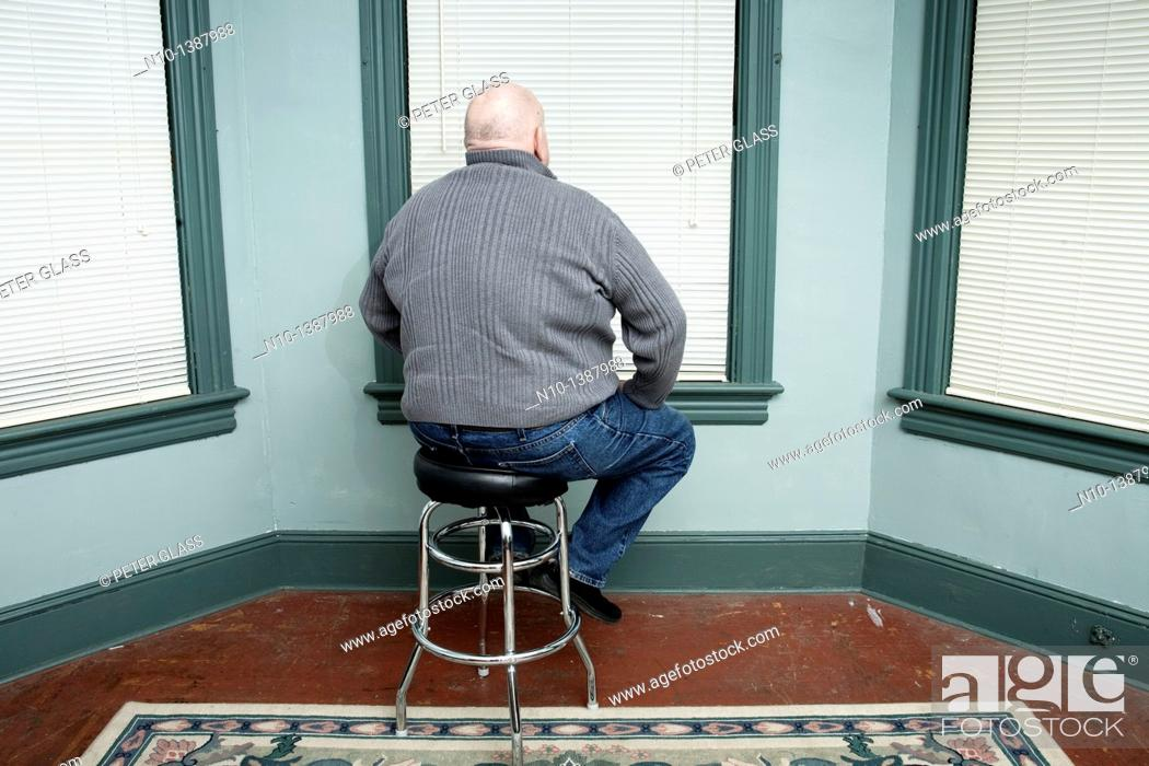 Stock Photo: Older man sitting on a stool, facing a window.