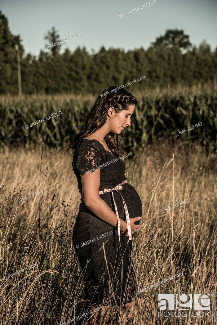 Stock Photo: Schwangere Frau steht auf einem Feld.
