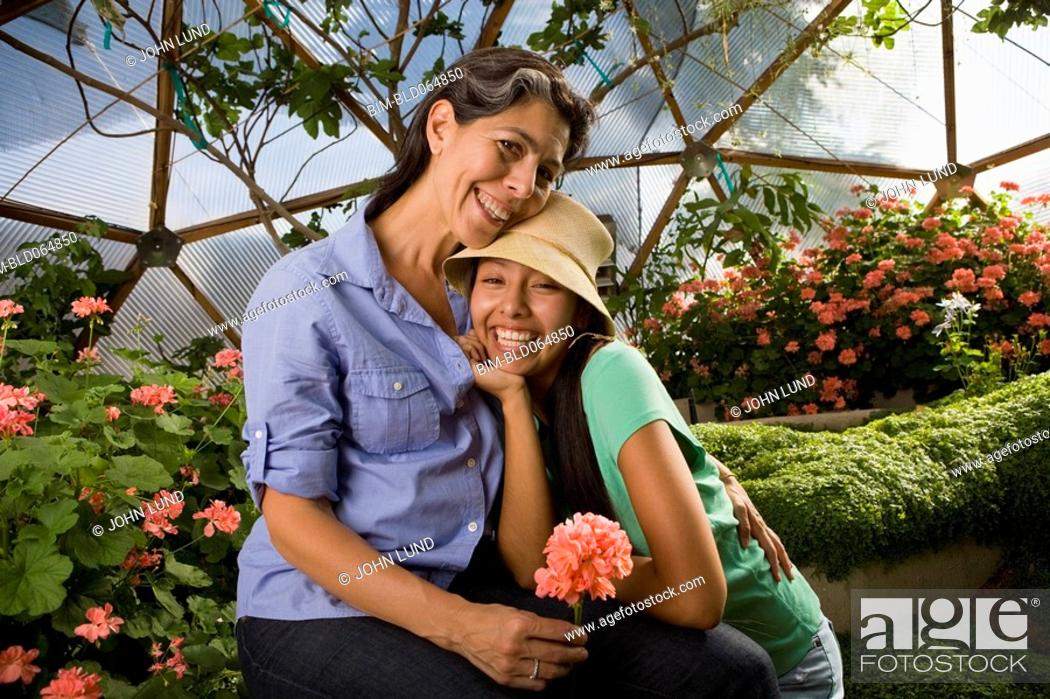 Stock Photo: Mother and daughter hugging in conservatory.