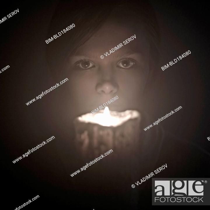 Stock Photo: Caucasian woman holding candle near face.