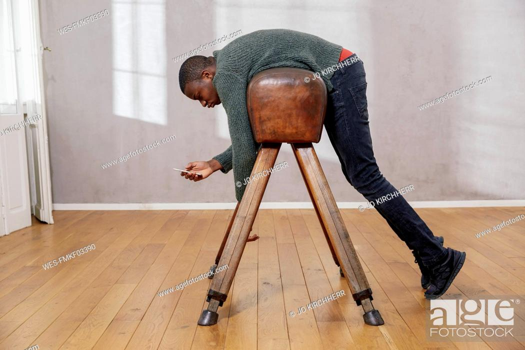 Imagen: Young man hanging out on pommel horse looking at smartphone.