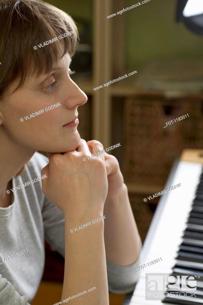 Stock Photo: A woman leaning on an upright piano, looking pensive.