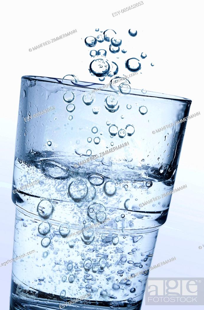 Stock Photo: A glass of fresh clear water and lots of sparkling carbonic acid.