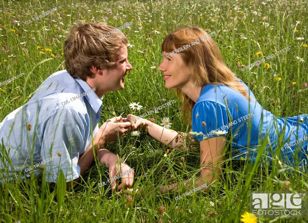 Stock Photo: man, woman lying in grass with flowers.