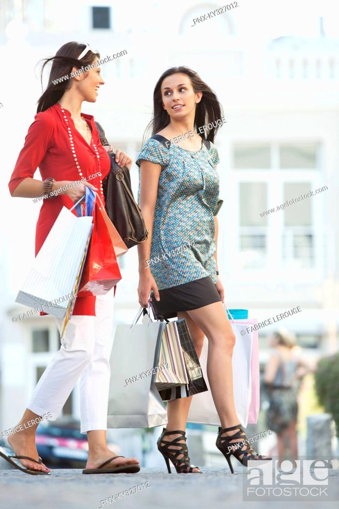 Stock Photo: Two young women walking with shopping bags.
