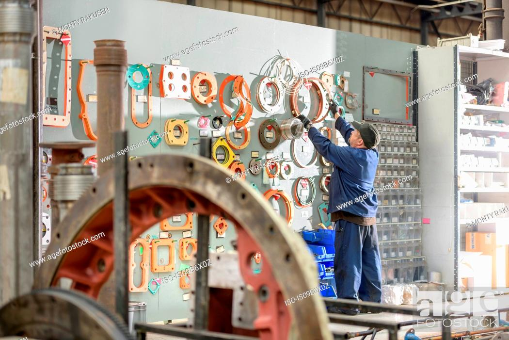 Stock Photo: Locomotive engineer picking gaskets and seals in train works.