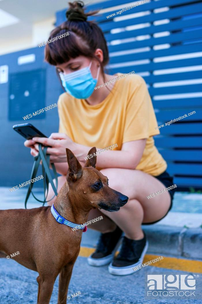 Stock Photo: Woman wearing face mask using mobile phone while crouching by dog at sidewalk during coronavirus outbreak.