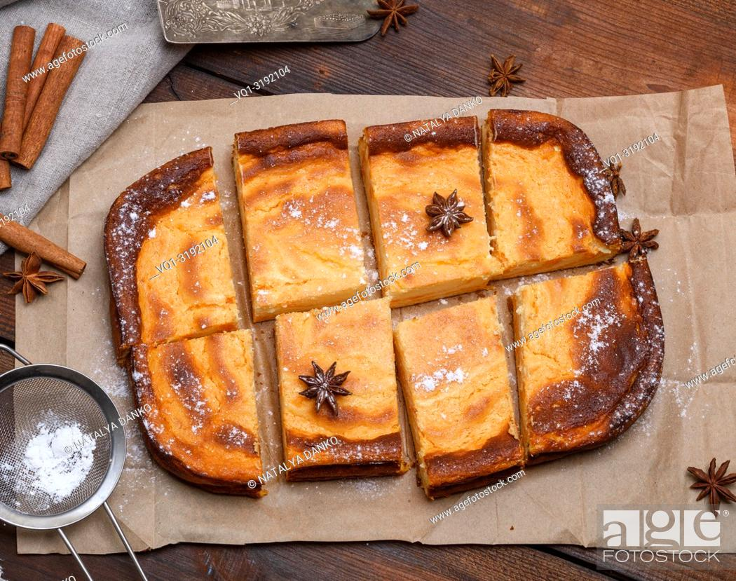 Imagen: cut into pieces of a rectangular cake of cottage cheese and pumpkin on brown paper, top view.