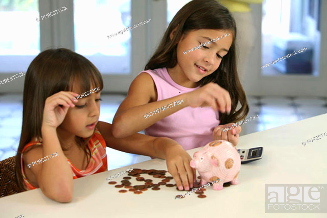 Stock Photo: Two sisters counting coins from a piggy bank.