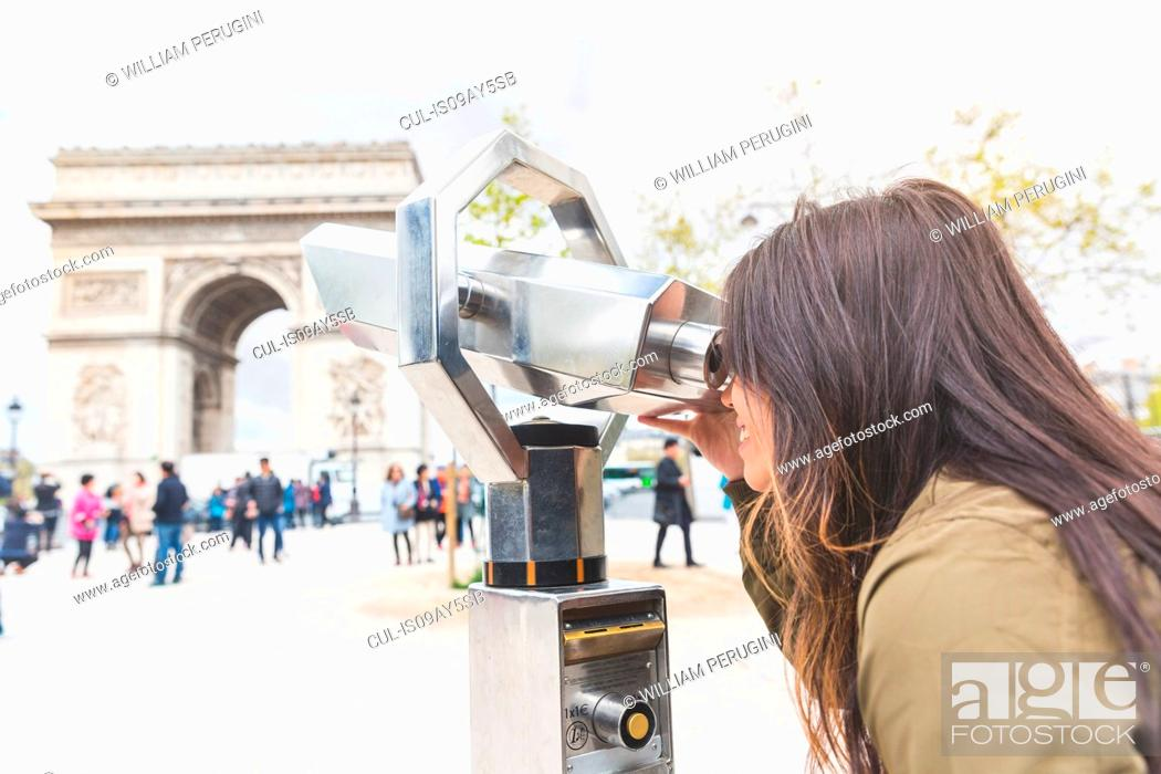 Stock Photo: Young woman looking through coin binoculars at Arc de Triomphe, Paris, France.