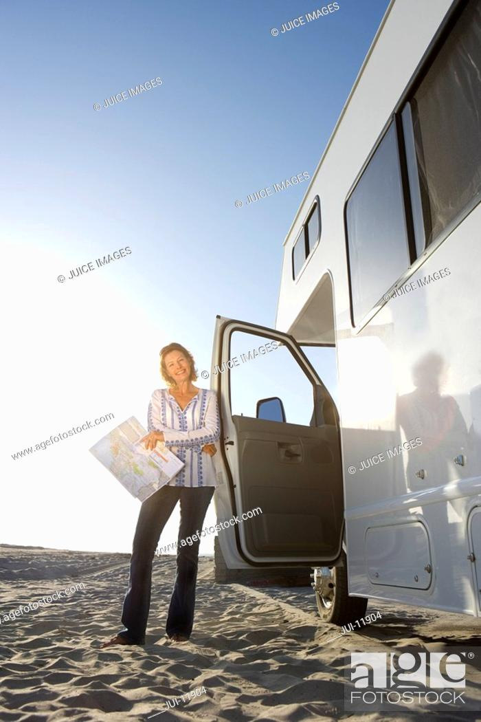 Stock Photo: Mature woman with map by motor home on beach, low angle view lens flare.