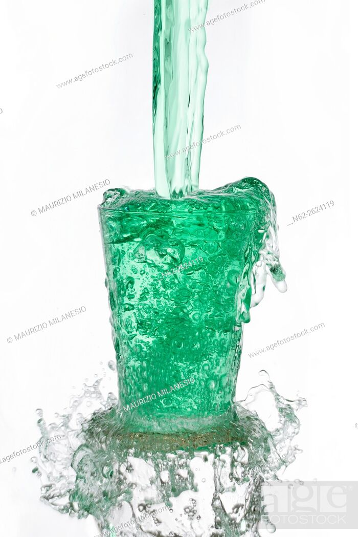 Stock Photo: Green drinks poured vigorously overflowing splashing from a glass, on a white background.