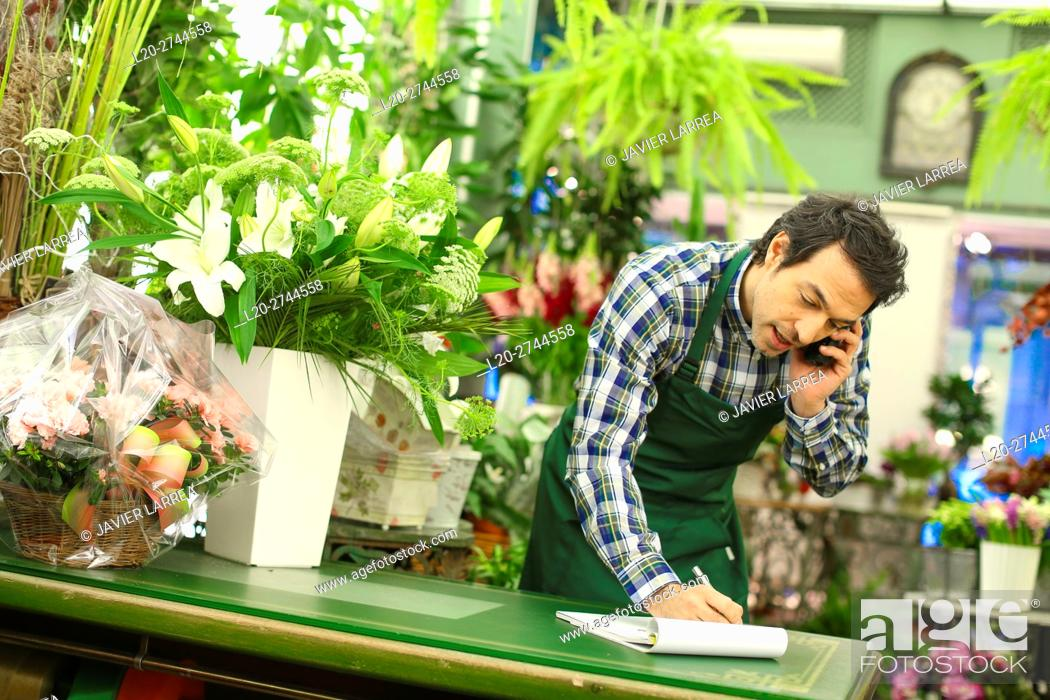 Stock Photo: Florist in flower shop taking an order from a customer on the phone.