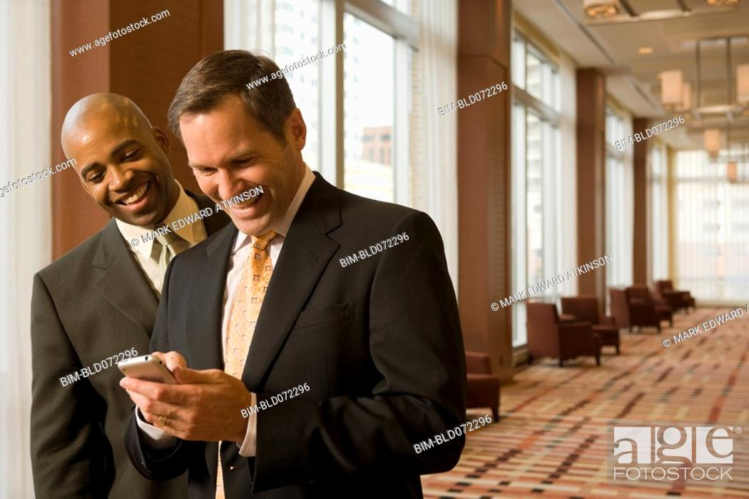 Stock Photo: Multi-ethnic business people looking at cell phone in corridor.