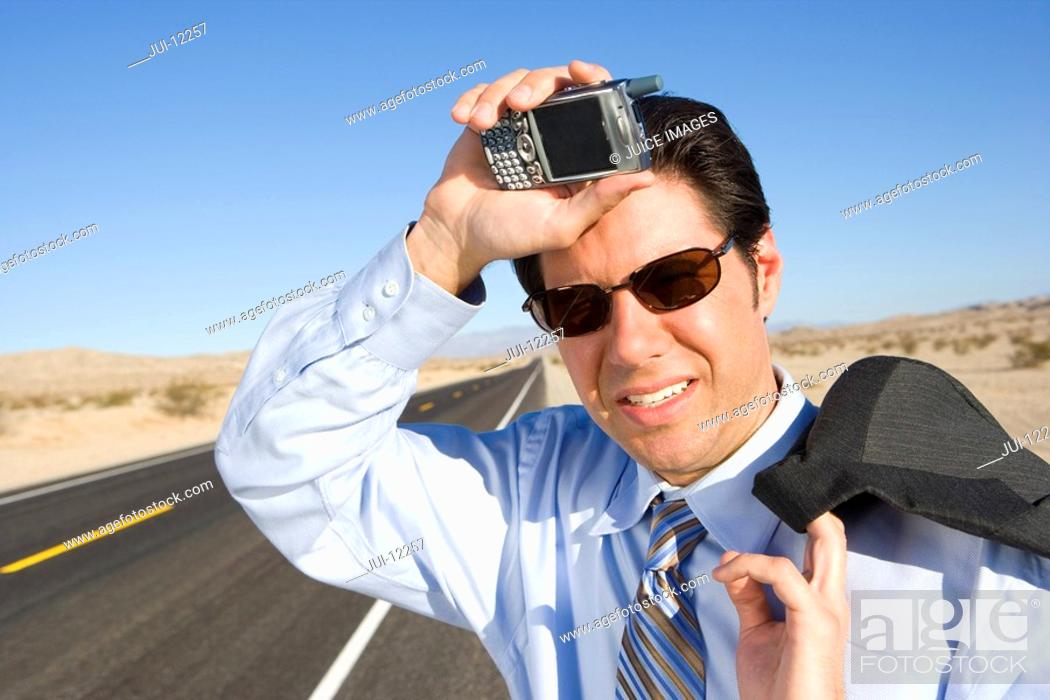 Stock Photo: Businessman in sunglasses with mobile phone on side of road, hand to head, smiling, close-up.