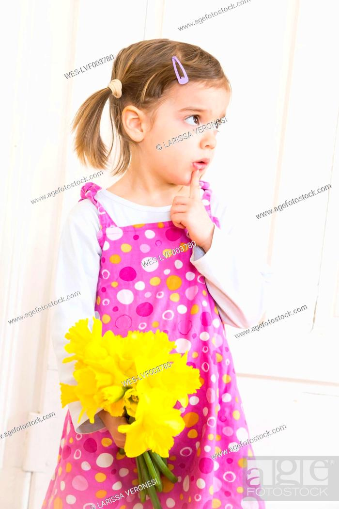 Stock Photo: Portrait of little girl with bunch of daffodils.