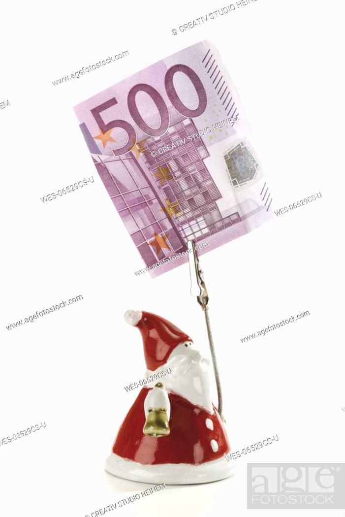 Stock Photo: Santa Claus Figurine holding Euro note.
