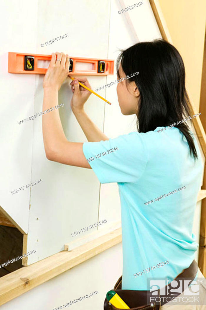 Stock Photo: Side profile of a young woman using a spirit level to mark on a wall.
