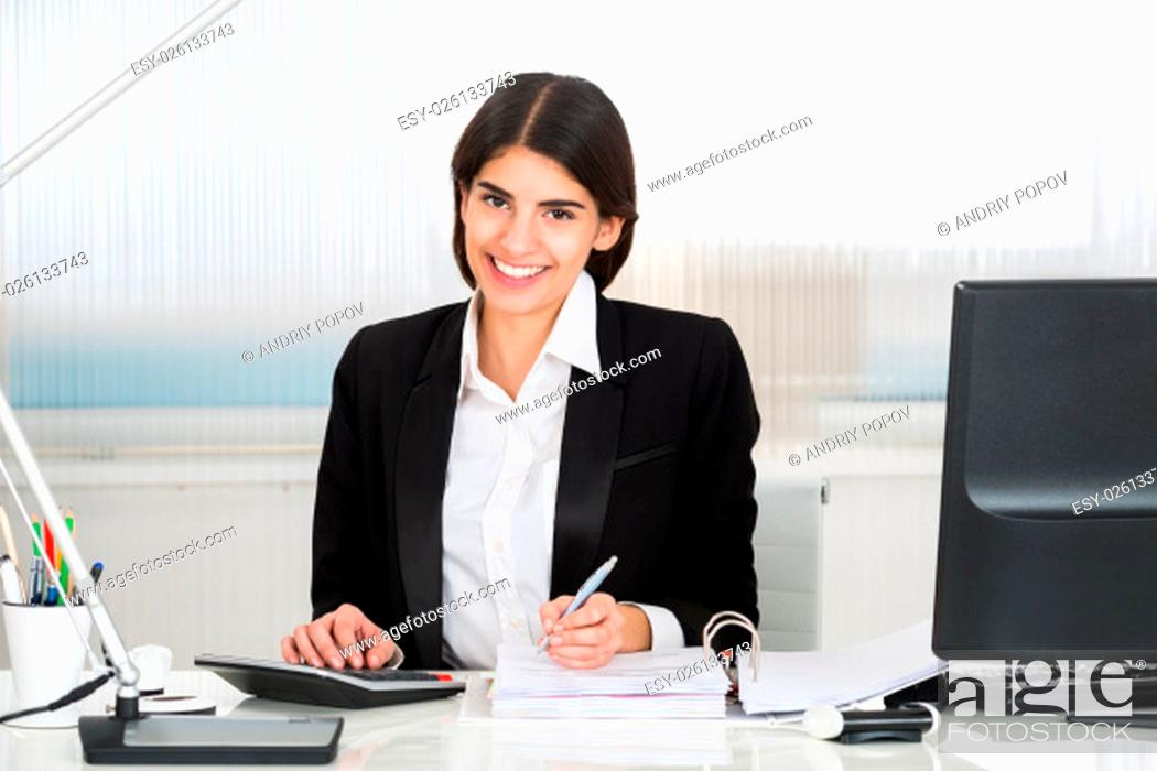 Stock Photo: Young female accountant calculating finance with calculator at desk in office.