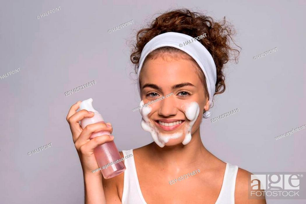 Stock Photo: A portrait of a young woman cleaning face in a studio, beauty and skin care.