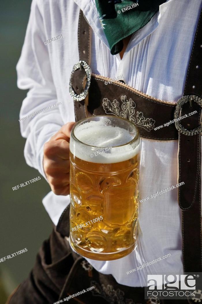 Stock Photo: Detail of man in traditional Bavarian, Lederhosen, holding litre glass of beer.