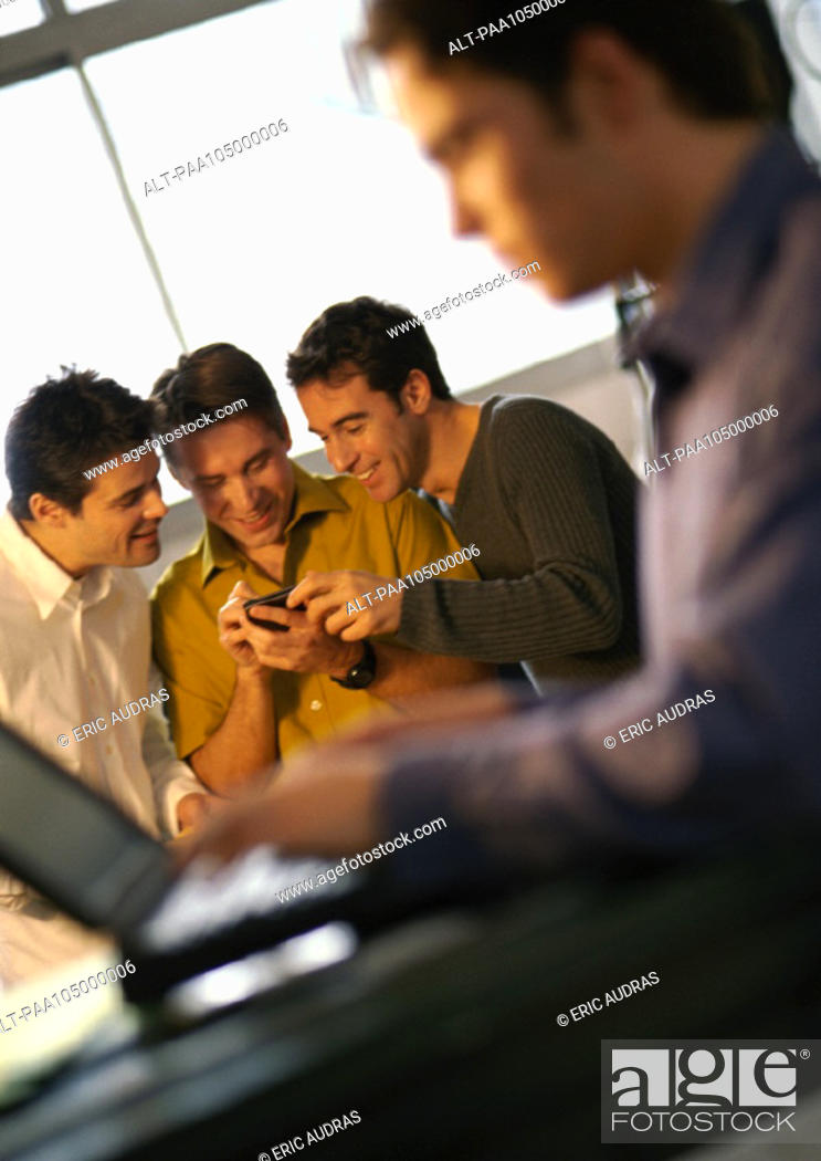 Stock Photo: Three men looking at hand held computer, fourth man using laptop in foreground.