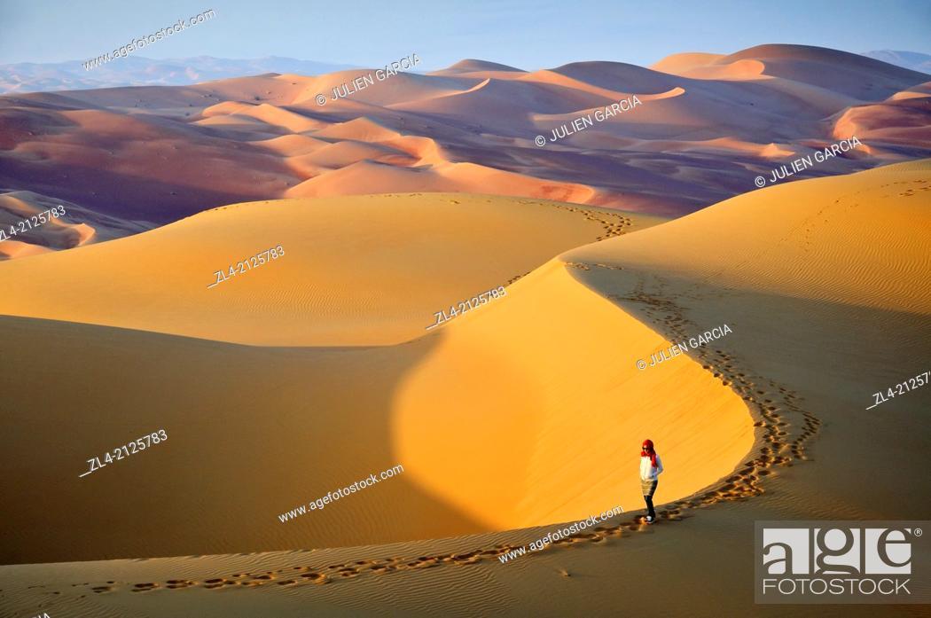 Stock Photo: Woman in the sand dunes of the empty quarter desert. United Arab Emirates, UAE, Abu Dhabi, Liwa Oasis, Moreeb Hill, Tal Mireb. Model Released.