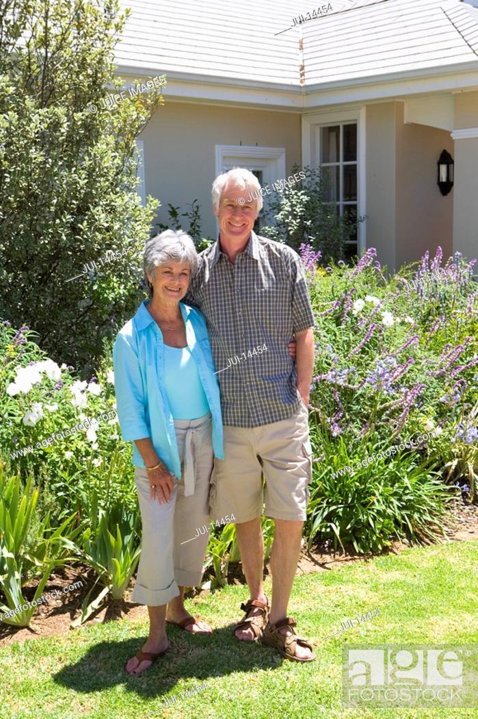 Stock Photo: Senior couple in garden, smiling, portrait.