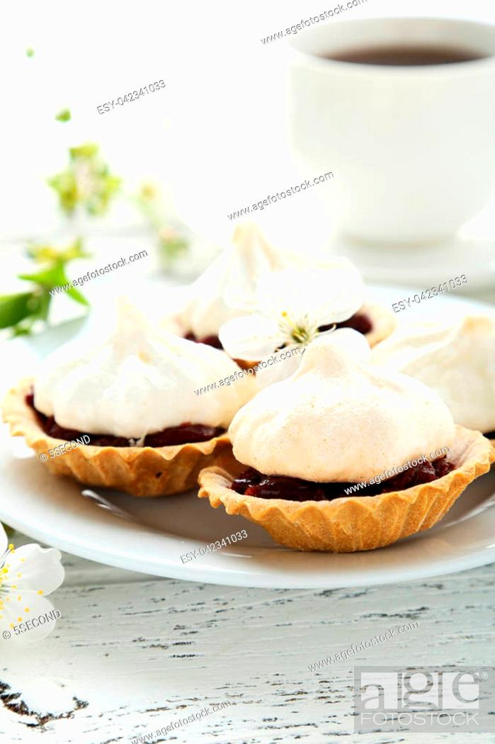 Stock Photo: French meringue cookies in tartlet on white wooden background.