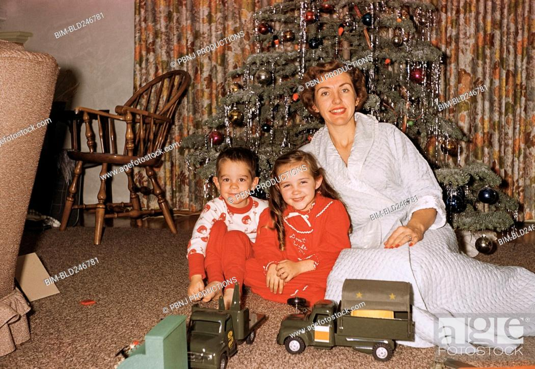 Stock Photo: Caucasian mother posing with son and daughter near Christmas tree.