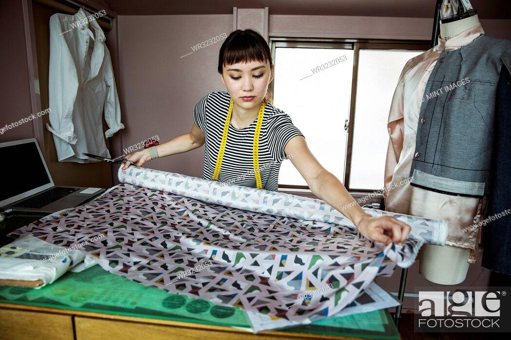 Stock Photo: Japanese female fashion designer working in her studio, measuring fabric.